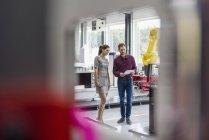 Бизнесмен и женщина встречаются перед промышленными роботами в высокотехнологичной компании — стоковое фото