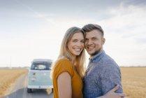 Retrato de una joven pareja sonriente en camper van en el paisaje rural - foto de stock