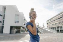 Нидерланды, Маастрихт, улыбающаяся молодая женщина по мобильному телефону в городе — стоковое фото