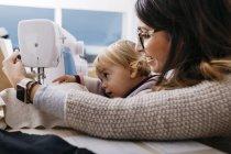 Glückliche Mutter mit kleiner Tochter zu Hause mit Nähmaschine — Stockfoto