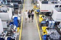 Three women with tablet walking and talking in factory shop floor — Stock Photo