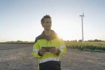 Engenheiro em pé na paisagem rural em uma turbina eólica e segurando tablet — Fotografia de Stock