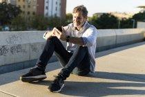Sonriendo hombre maduro sentado en la ciudad y usando el teléfono celular - foto de stock