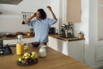 Woman dancing and listening music in the morning in her kitchen — Stock Photo