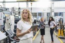 Женщина держит планшет в цехе завода с двумя женщинами на заднем плане — стоковое фото