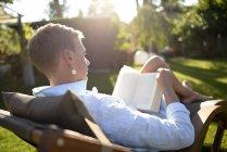 Woman on deckchair reading book in the garden — Stock Photo