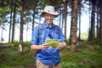 Hombre sonriente mirando el mapa durante una caminata en el bosque - foto de stock