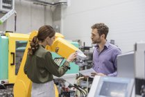 Businessman and woman having a meeting in front of industrial robots in a high tech company — Stock Photo