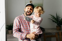 Padre sosteniendo a su hija pequeña en su brazo, jugando con su teléfono inteligente. - foto de stock