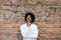 Homme afro-américain debout devant un mur de briques, levant les yeux, souriant — Photo de stock