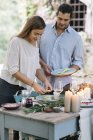 Couple preparing a romantic candlelight meal outdoors — Stock Photo