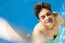 Portrait of young woman relaxing in swimming pool — Stock Photo
