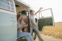 Jeune couple avec téléphones cellulaires se détendre au camping-car dans le paysage rural — Photo de stock