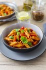 Top view of Penne pasta with tomato and basil leaves in bowls — Stock Photo