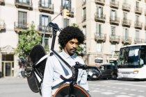 Hombre afroamericano llevando su bicicleta sobre sus hombros en la ciudad - foto de stock