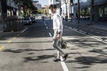 Jovem na cidade cruzando rua e levando saco — Fotografia de Stock