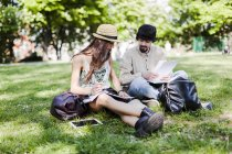 Two students sitting on a meadow in a park and looking at notes — Stock Photo