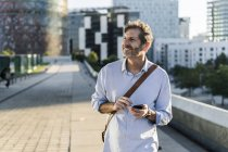 Smiling mature man with cell phone in the city — Stock Photo