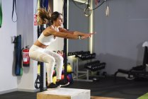 Woman doing box jumps in a gym — Stock Photo