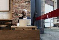 Старший бізнесмен, що працює на ноутбуці в кафе — стокове фото