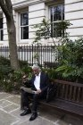 Empresário sênior sentado no banco ao ar livre e trabalhando no laptop — Fotografia de Stock