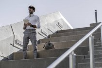 Молодой человек стоит на лестнице и держит планшет — стоковое фото