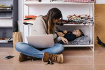 Mother sitting on the floor at home using laptop with little daughter lying in shelf — Stock Photo