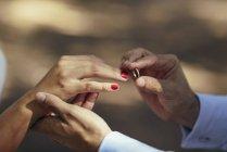 Наречений поклавши Весільні кільця на палець нареченої, крупним планом — стокове фото