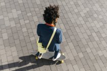 Young businessman riding skateboard on a square — Stock Photo