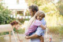 Père câlin avec fille dans le jardin — Photo de stock