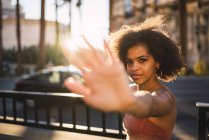 USA, Nevada, Las Vegas, portrait of young woman in the city in backlight raising her hand — Stock Photo