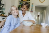 Happy mother and daughter sitting at kitchen table at home — Stock Photo
