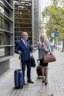 Senior hombre de negocios y mujer de negocios con equipaje sobre la marcha en la ciudad - foto de stock
