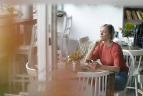 Young woman with cell phone sitting at table in a cafe — Stock Photo