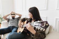 Couple détendu assis sur un canapé, femme jouant de la guitare à la maison — Photo de stock