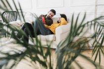 Пара сидить на дивані у вітальні нового дому і дивиться на мобільний телефон. — стокове фото