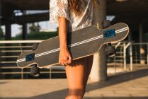 Close-up of woman holding skateboard in the city — Stock Photo