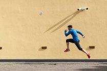Uomo sportivo che si esercita a parete gialla con telecamera a circuito chiuso — Foto stock