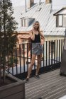 Serious blond woman on the phone standing on roof terrace — Stock Photo