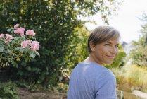 Portrait de femme souriante dans le jardin tournant autour — Photo de stock