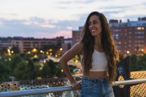 Linda jovem sorridente com cabelos castanhos longos na cidade ao entardecer — Fotografia de Stock