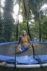 Retrato de mulher sorridente sentado no trampolim no jardim — Fotografia de Stock