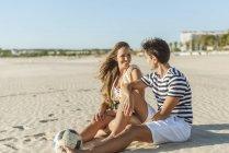 Улыбающаяся молодая пара, сидящая на пляже с мячом — стоковое фото