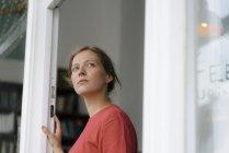 Giovane donna alla porta francese in un caffè guardando intorno — Foto stock