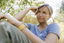 Mujer sentada en el jardín en silla - foto de stock