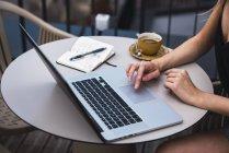 Mujer joven sentada en el balcón y trabajando en el ordenador portátil, vista parcial - foto de stock