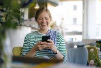 Сміється молода жінка, що дивиться на стільниковий телефон в кафе — стокове фото