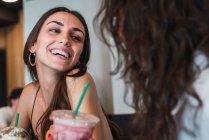Портрет счастливой молодой женщины в кофейне, веселящейся со своим другом — стоковое фото