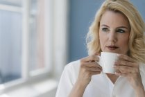 Portrait of blond woman drinking coffee at the window — Stock Photo