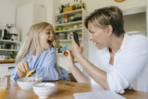 Happy mother and daughter having fun at table at home and taking smartphone picture — Stock Photo